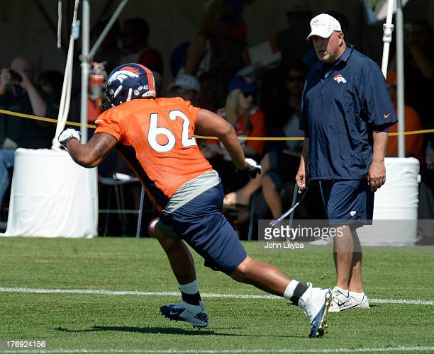 Denver Broncos offensive line coach Dave Magazu watches Manase Foketi hit the blocking dummy during practice August 19 2013 at Dove Valley
