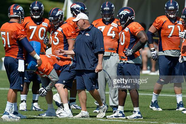 Denver Broncos offensive line coach Dave Magazu with the offensive line during practice August 19 2013 at Dove Valley