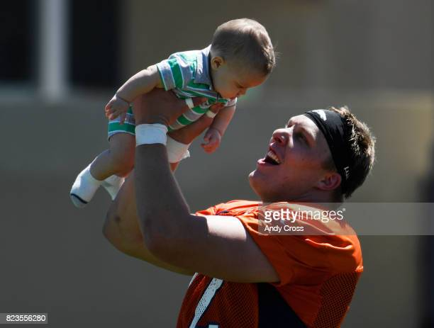 Denver Broncos offensive tackle Garett Bolles lifts his son Kingston in the air after the first day of training camp at Dove Valley July 26 2017