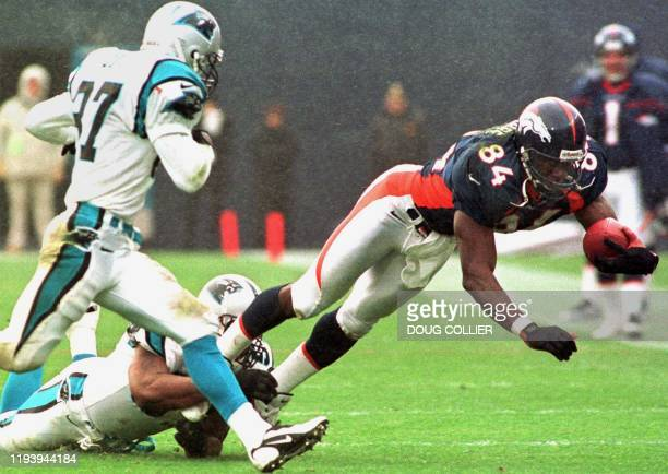 Denver Broncos player Shannon Sharpe dives for a first down past Carolina Panthers defenders Lamar Lathon and Chad Cota during first half action of...
