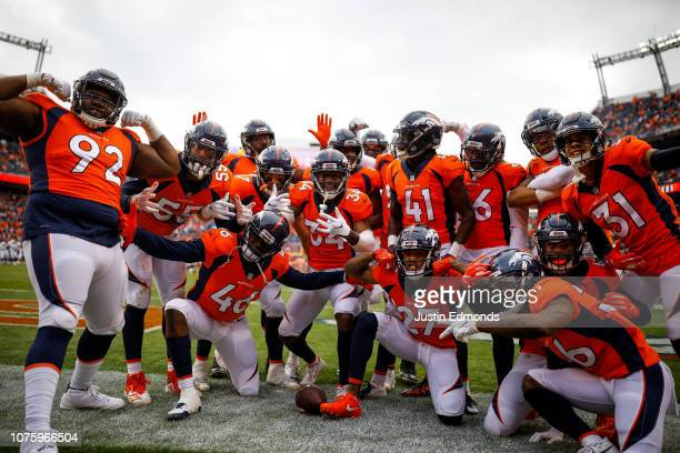 Denver Broncos players celebrate after a first quarter interception by cornerback Isaac Yiadom during a game against the Los Angeles Chargers at...