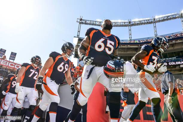 Denver Broncos players including Ronald Leary run onto the field to warm up before a game against the Tennessee Titans at Empower Field at Mile High...
