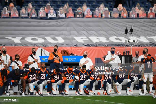 Denver Broncos players lock arms and kneel during the national anthem before a game against the Tennessee Titans at Empower Field at Mile High on...
