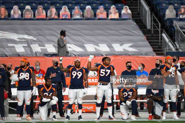 Denver Broncos players lock arms, kneel, and hold up fists during the national anthem before a game against the Tennessee Titans at Empower Field at...