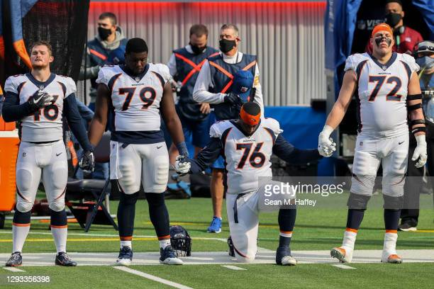 Denver Broncos players stand and kneel during the national anthem before playing against the Los Angeles Chargers at SoFi Stadium on December 27,...