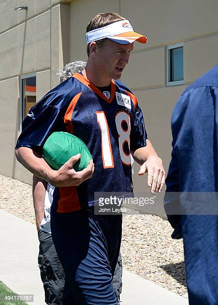 Denver Broncos QB Peyton Manning walks to the podium for his press conference carrying a green football after practice May 28 2014 at Dove Valley...