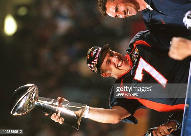 Denver Broncos quarterback John Elway holds the Vince Lombardi trophy as coach Mike Shanahan looks on after the Broncos defeated the Green Bay...