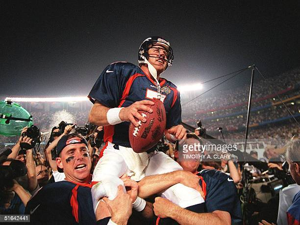 Denver Broncos quarterback John Elway is carried by teammates Ed McCaffrey and Bubby Brister after the Broncos defeated the Green Bay Packers 31-24...