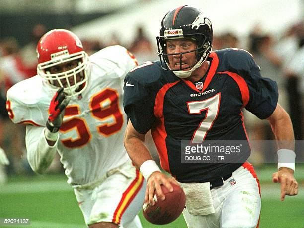 Denver Broncos quarterback John Elway scrambles for yardage as he is pursued by Kansas City Chiefs linebacker Donnie Edwards during the Broncos...