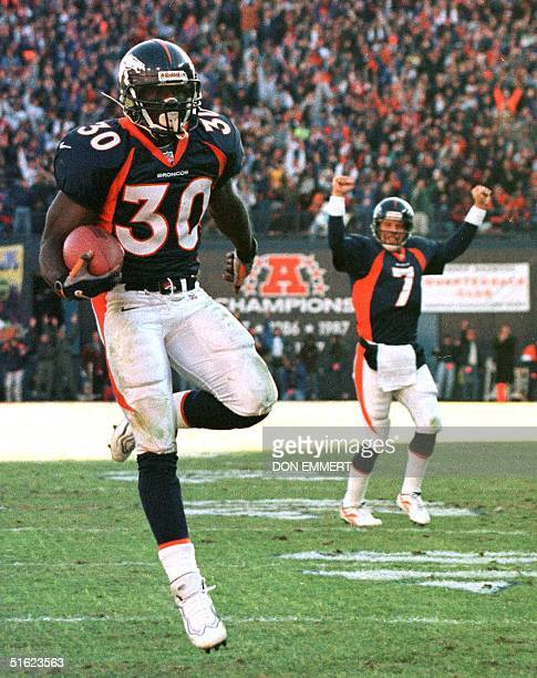 Denver Broncos quarterback John Elway signals a touchdown as running back Terrell Davis runs for his second touchdown of the day against the Miami...