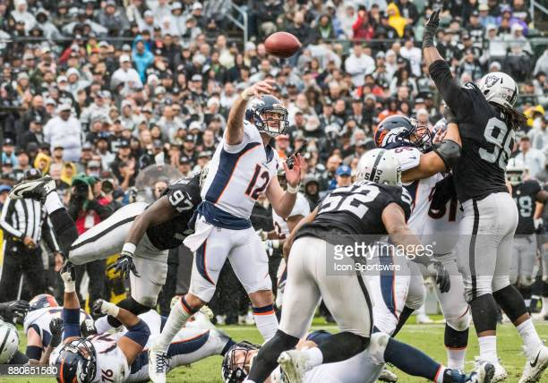 Denver Broncos quarterback Paxton Lynch lofts a pass over Oakland Raiders defensive end Denico Autry during the game between the Denver Broncos...