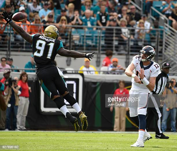 Denver Broncos quarterback Paxton Lynch throws a pass over the out stretch arm of Jacksonville Jaguars defensive end Yannick Ngakoue during the first...