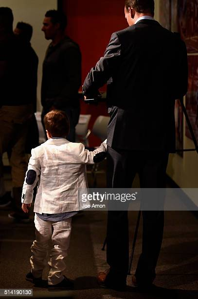 Denver Broncos quarterback Peyton Manning and his 4 year old son Marshall walk away from the podium after a press conference to announce his...