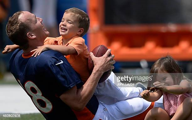 Denver Broncos quarterback Peyton Manning has a little fun with his son Marshall who tackles him and his daughter Mosley after practice on day four...