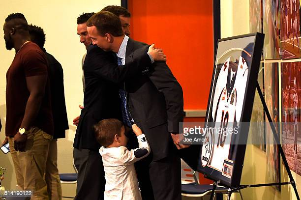 Denver Broncos quarterback Peyton Manning hugs his older brother Cooper with his 4 year old son Marshall after a press conference to announce his...