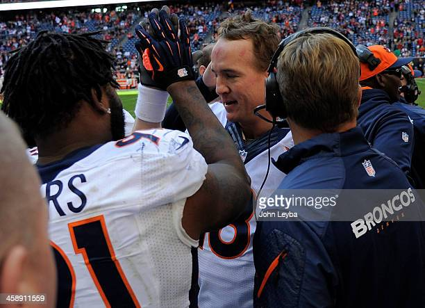 Denver Broncos quarterback Peyton Manning is congratulated by Denver Broncos defensive end Robert Ayers after throwing his 51st touchdown pass to...