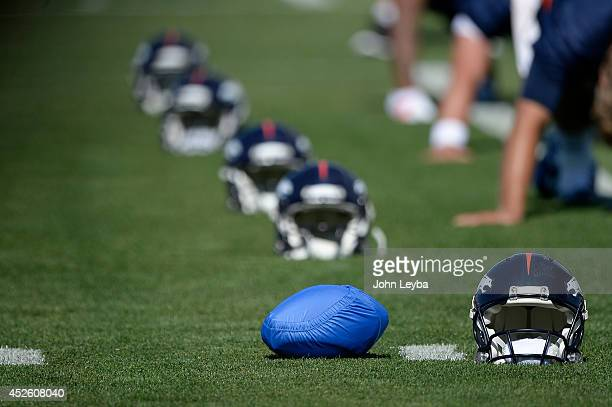Denver Broncos quarterback Peyton Manning sets his football in a blue cover next to his helmet during the start of the Denver Broncos 2014 training...