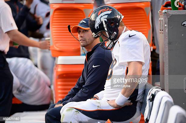 Denver Broncos quarterback Peyton Manning sit son the bench with offensive coordinator Adam Gase during the fourth quarter December 14 2014 at...