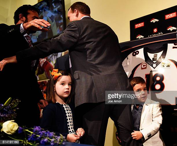 Denver Broncos quarterback Peyton Manning's 4 year old twins Mosley and Marshall hang onto daddy's leg after a press conference to announce his...