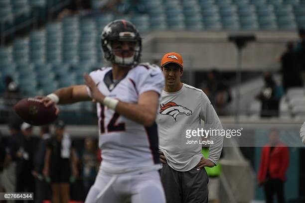 Denver Broncos quarterback Trevor Siemian watches Denver Broncos quarterback Paxton Lynch during pregame warm ups against the Jacksonville Jaguars...