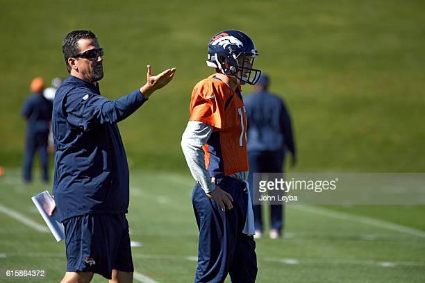 Denver Broncos quarterbacks coach Greg Knapp instructs during drills as Denver Broncos quarterback Trevor Siemian looks on during practice October 20...