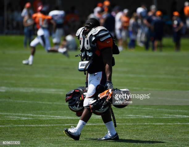 Denver Broncos rookie running back De'Angelo Henderson carries other player's gear into the locker room as per tradition for rookies at training camp...