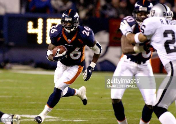 Denver Broncos running back Clinton Portis breaks through a hole in the Oakland Raiders defense in the first half 11 November 2002 in Denver CO AFP...
