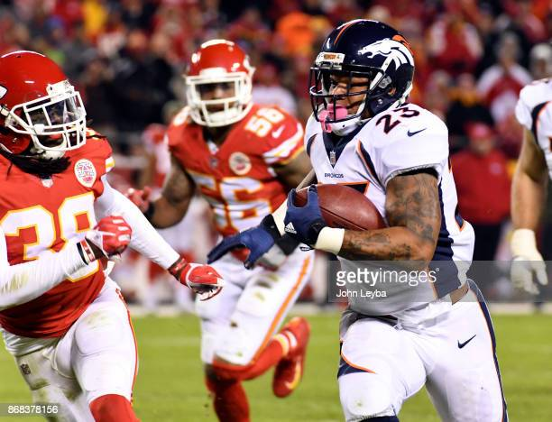 Denver Broncos running back Devontae Booker picks up a big gain as Kansas City Chiefs free safety Ron Parker comes in for the tackle during the third...