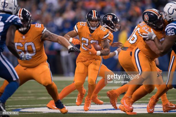 Denver Broncos running back Devontae Booker runs through a opening in the line during the NFL game between the Denver Broncos and Indianapolis Colts...