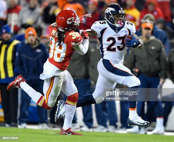 Denver Broncos running back Devontae Booker stiff arms Kansas City Chiefs free safety Ron Parker on a first down run in the third quarter during...