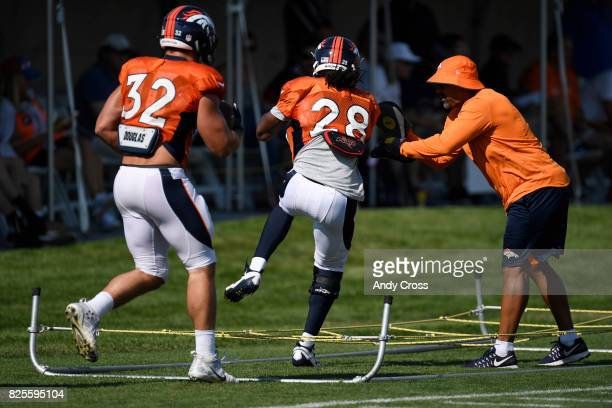 Denver Broncos running back Jamaal Charles and Denver Broncos fullback Andy Janovich run the rope ladder during training camp at Dove Valley August...