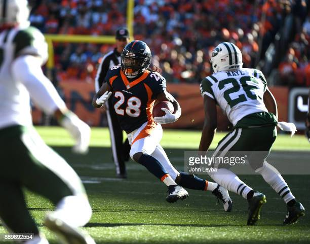 Denver Broncos running back Jamaal Charles picks up a few yards as New York Jets free safety Marcus Maye comes in for the stop during the first...