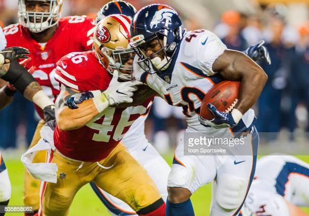 Denver Broncos running back Juwan Thompson fights off San Francisco 49ers tight end Cole Hikutini as he races towards the end zone during the...