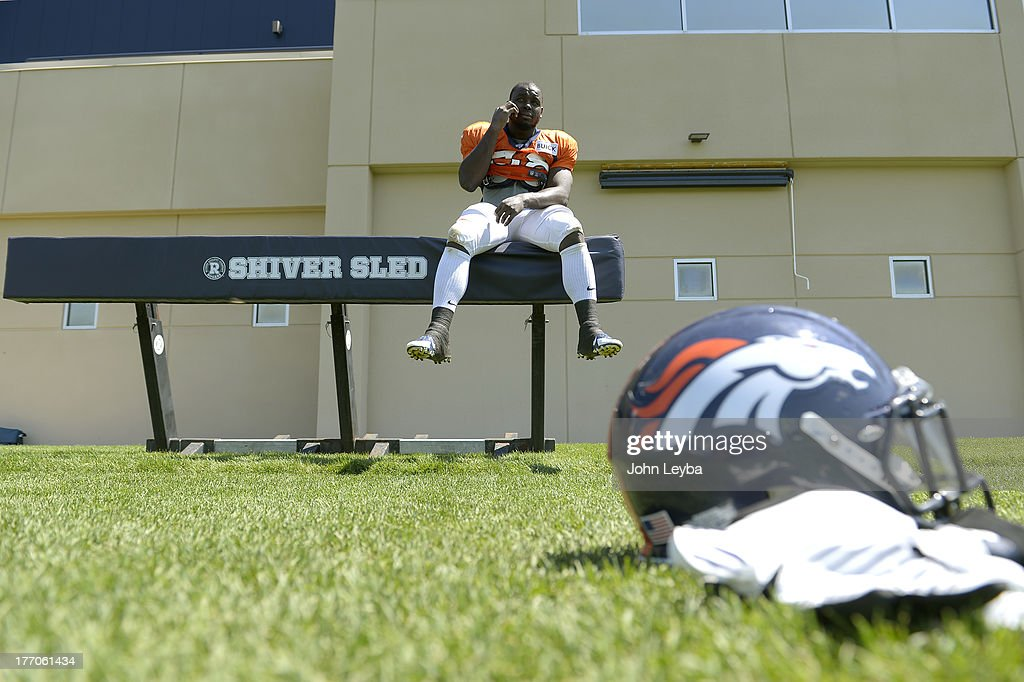 Denver Broncos running back Montee Ball (38) sits on the sled as he conducts an interview on the phone after practice August 20, 2013 at Dove Valley