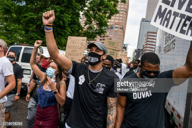 Denver Broncos safety Justin Simmons holds his fist in the air as he marches at a protest for the death of George Floyd on June 6 2020 in Denver...