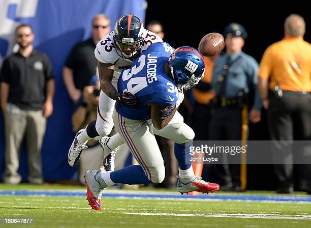 Denver Broncos strong safety Duke Ihenacho puts a big hit on New York Giants running back Brandon Jacobs to jar the ball loose for an incomplete pass...