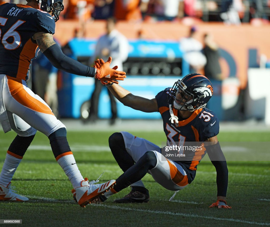 Denver Broncos strong safety Justin Simmons (31) is helped up by outside linebacker Shane Ray (56) during the first quarter against the New York Jets on December 10, 2017 in Denver, Colorado at Sports Authority Field at Mile High Stadium. Simmons left the game with an ankle injury on this play.