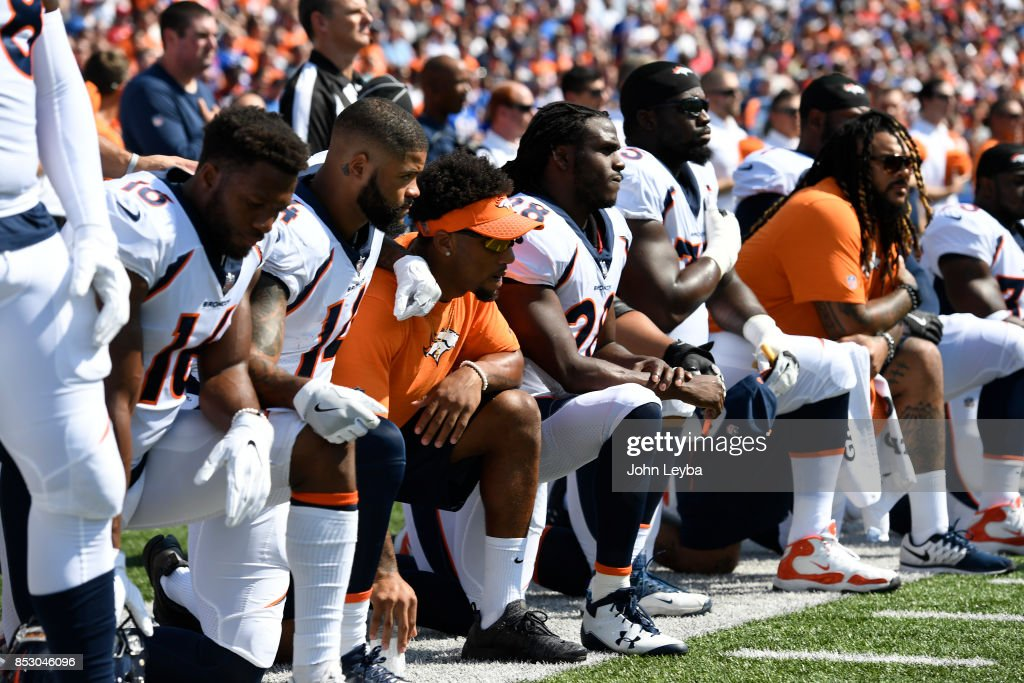 Denver Broncos team take a knee during the national anthem