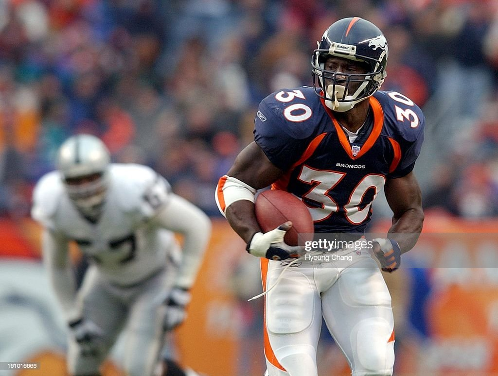 Denver Broncos Terrell Davis controls the ball against Oakland Raiders deffense in the 1st quarter at Denver on Sunday. Denver won 23-17. (The Denver Post/ Hyoung Chang) : News Photo