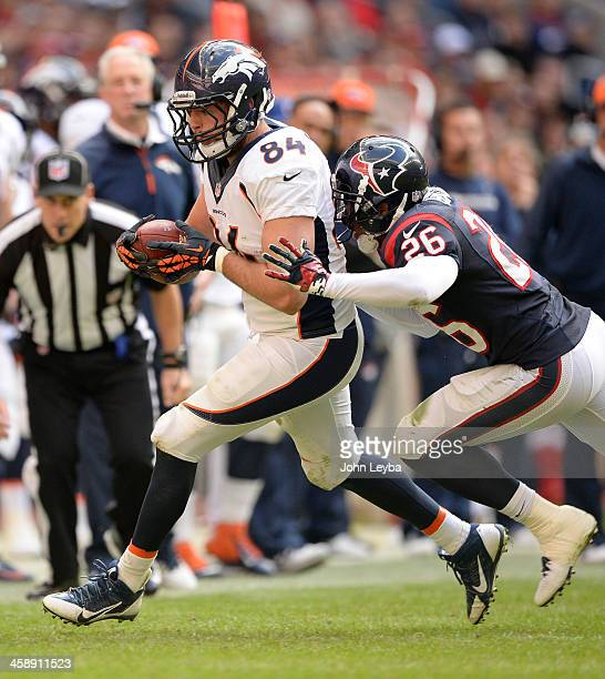 Denver Broncos tight end Jacob Tamme catches a pass for a first down as Houston Texans defensive back Brandon Harris shoves him out of bounds during...