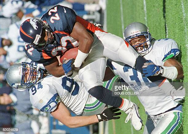 Denver Broncos Vaughn Hebron is brought down by Seattle Seahawks Bennie Blades as teammate Chad Brown looks on during the first half 02 November at...