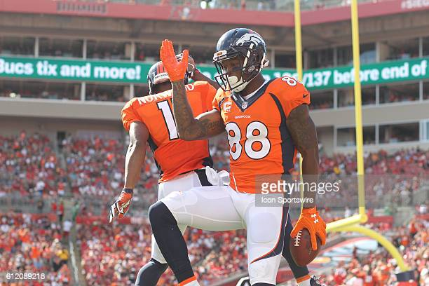 Denver Broncos wide receiver Demaryius Thomas leaps in the air and celebrates with Jordan Norwood during the regular season game between the Denver...