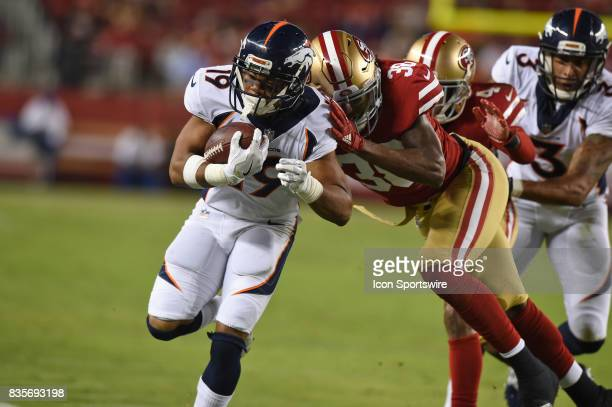 Denver Broncos Wide Receiver Kalif Raymond runs the ball and is tackled by San Francisco 49ers Safety Adrian Colbert during an NFL preseason game...