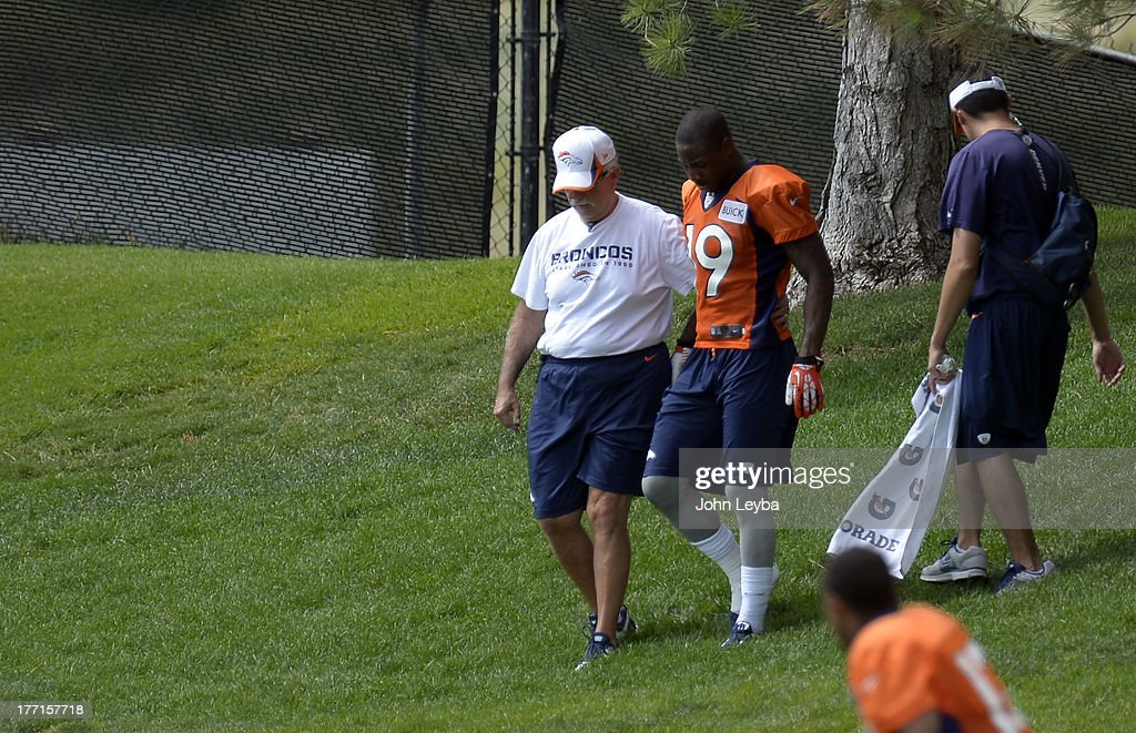 Denver Broncos wide receiver Lamaar Thomas (19) walks off with head trainer Steve Antonopulos after going down with an injury after catching a pass during practice August 22, 2013 at Dove Valley