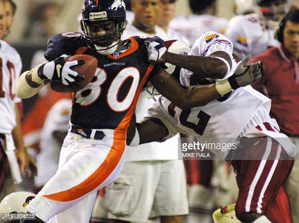 Denver Broncos' wide receiver Rod Smith is hauled down by Arizona Cardinals cornerback Tom Knight during the second quarter 23 September 2001 in...