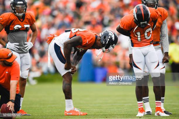 Denver Broncos wide receivers Demaryius Thomas adjusts his pants as he and Emmanuel Sanders wait for their turn to run routes during training camp on...
