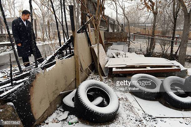 Denver City Councilman Paul Lopez examines an illegal dump site where a fence had been torched in an alley in the Westwood neighborhood of Denver CO...