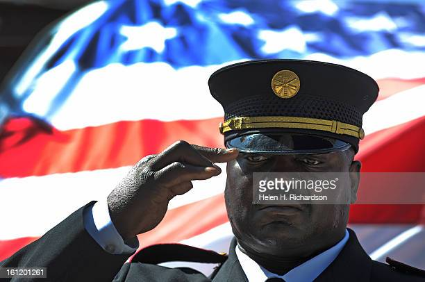 Denver CO September 11 2011 Engineer Larry Holmes with the City of Aurora Fire and honor guard salutes during the playing of taps Behind him is the...