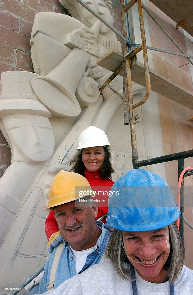 Denver, Colo. Oct. 30, 2001 -- Sculptors Madeline Wiener, front, Roger Seal and Kathleen Caricof pause while doing the finishing work on one of two 40-foot sculptures on the new Lamont School of Music building on the DU Campus. The panels are carved from  : News Photo