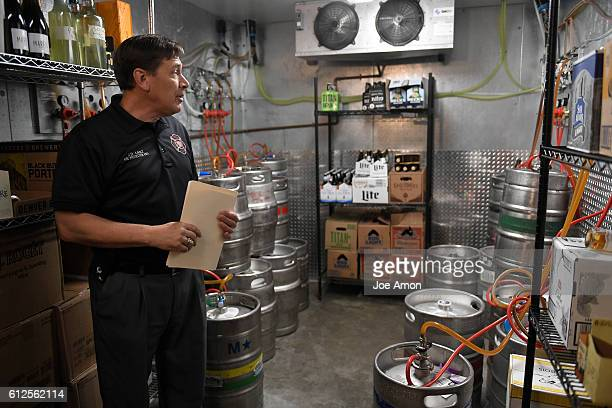 Denver fire protection engineer JD Lanz reads a gauge as he explains to Racines Restaurant owner David Racine why there will be new sensors lights...